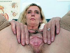 Lusty mature nurse shows off while stretching and stimulating her pussy