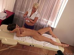 Watch this hottie getting a massage from her horny masseuse before they end up having an oiled up lesbian moment.