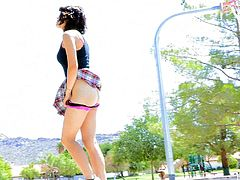 Kinky dark-haired chick Raven wearing a miniskirt is walking in a park. She sits down on a bench and decides to play with her pussy while there's no one around.