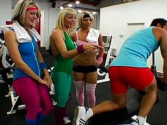Three lovely chicks in sportswear undress their muscled fitness instructor. Girls give him a handjob and then get fucked in a CFNM video.