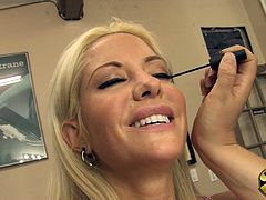 Helly Mae Hellfire flashes her brilliant smile and fantastic cleavage while getting her makeup done before a film shoot.