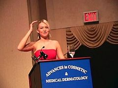Charming blonde babe in a red dress lifts a dress up to show her hot ass in a conference hall. She also rehearses her speech and masturbates on the stage.