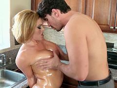 Entertain yourself by watching this blonde cougar covered in oil, with big knockers wearing a thong, while she gets drilled in the kitchen.