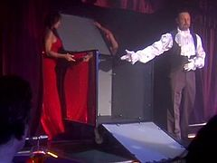 Click to watch this brunette MILF, with giant breasts wearing a red dress, while she gets fucked hard after helping her partner to do a show.