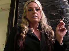 In the first part of the video some blond MILF smokes a cigarette in a backstage. In the part number two some slim blondie prepares to play her role in the gloryhole room.