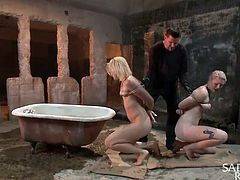 There are two blonde girls naked and strongly tied up in a deserted room. One of them is flexible and keeps hanging from the ceiling. You cannot skip noticing the presence of a bath tub. Want to find what's the use of this? A man shows up, to sink the blonde´s head in the tub