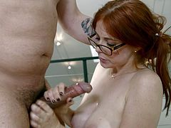 This redhead slut likes all the kinky action she can get. She sucks cock and she shows she can take it deep in her throat so she gets face fucked. The big cock goes from the back of her mouth into her bosom.