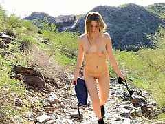 Sizzling blonde chick walks in the mountains. It is very hot there, so she takes off her clothes. This babe shows off her natural boobs and ass while walking.