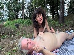 This young brunette babe was walking around the forest when she stumbled upon an old couple. The mature woman was giving her husband a blowjob. She joined them and rode his old cock.