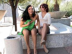 Two brunette girls walks in the street showing their sexy legs. These hotties take their panties off and start to play with each others nice pussies.