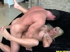 Have fun watching this blonde cougar, with a nice ass and gigantic knockers, while she gets drilled hard by a touch fellow over a couch.