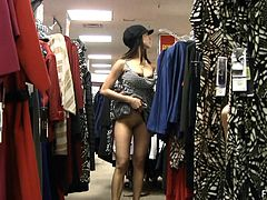 Sexy Shelbie is doing shopping in a clothing store. This naughty chick lifts a dress up right there. She shows off the ass and plays with her pussy.