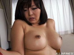 A hot Japanese MILF takes off her dress in a living room. She fondles her nipples and then gets toyed with a vibrator.