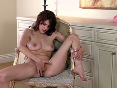 Redhead Bree Daniels fingers her pink pussy sitting on a chair