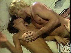 Get a load of this hot vintage video where these horny babes share this guy's big cock in a threesome in a living room.
