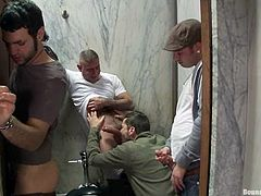 A few salacious gays are having fun in a public WC. They make a horny dude suck gloryhole weiners and then pound his butt doggy style by turns.