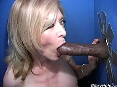 Salacious blonde mom Nina Hartley is a very experienced porn star, and she's gonna share her special skills in this clip. She sucks and rubs a black dick sticking out of a gloryhole and manages to milk it dry.