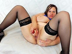 With her legs wide open is how mature Olena masturbates her creamy and juicy twat during her naughty solo