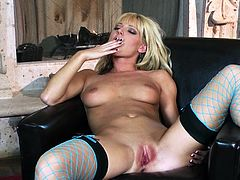 A blonde girl in lace lingerie and fishnets fondles her boobs. Then Niki sits down on an armchair. She shakes her booty and also plays with her hot pussy.