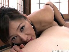A stunning Japanese MILF in a sexy lingerie stands on her knees in front of a guy. She gives him a blowjob expertly and also shows the boobs.