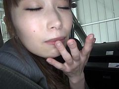 A pretty Japanese girl in office clothes lifts a skirt up to show her nice booty. She sucks a dick in a backseat and also gets a mouthful of cum.