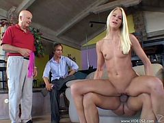 Get a boner watching this blonde babe, with a nice ass wearing a miniskirt, while she gets face fucked and pussy drilled in front of two horny men.