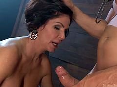 Do you love milfs? You gotta see this one in the video. The hot bitch is already naked and deprived from the liberty of moving as she's got her hands caught in a kind of torture machine. The brunette slut has big breasts and sucks cock well. See her getting fucked hard from behind with no mercy