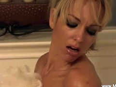 Milf Mia is a gorgeous blonde. She prepares a bath for herself. She sinks into the water and washes her huge boobs carefully with a bath sponge while teasing.
