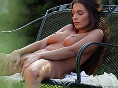 Drop dead gorgeous Lia relaxes in a chair in her backyard fully nude as she runs her hands all over her body and rubs her pussy.