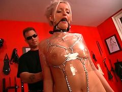 Hardcore bondage action by this young babe who loves wrapping herself with plastic all over her body. She keeps shut with a gag ball in her mouth while chains are all over her body including her face where the master jerks off all over her wrapped body