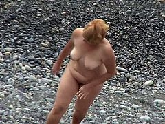 Watching her nude forms while mature lady enjoys the sun is causing voyeur a lot of pleasure