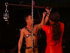 A dominant girl in latex trains her apprentice by having her practice sucking a chained male slave in this tube video.