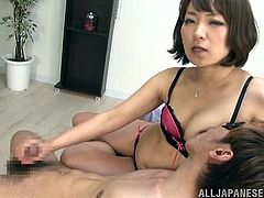 Horny Japanese mom wearing a bra is getting naughty with a guy indoors. They make out passionately and then the milf favours the guy with a handjob.