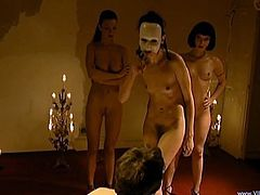 A tied up guy stands on all fours. Some girl in a mask drills his ass from behind with a strapon. After that he gets whipped by several girls.