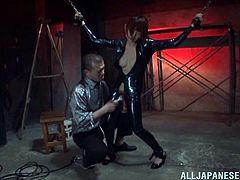 Salacious Japanese milf Mikoto Tsukawa wearing a latex overall is having fun with a dude in a basement. The stud ties Mikoto up and drills her twat with a dildo.