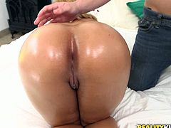 Curvaceous babe with big boobs and round booty poses for camera exposing her humps. Tarzan rubs her booty with oil feeling up her all over.