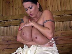 Breath taking babe with enormous size boobs masturbates her sweet looking pussy in the sauna. She also plays with her impressive assets and strokes her sweaty body.