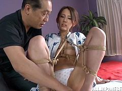 A tied up Japanese girl gets her pussy toyed with different vibrators by an old dude. Rumi Kamida also sucks one of the dildos.
