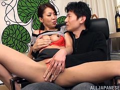 A slutty Japanese MILF pleases her boss in the office. She kisses him and gets her boobs licked. Then this horny woman gives a handjob and a blowjob.