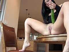 A pretty brunette girl fixes a big dildo to a table and rides it. Then she takes a big cucumber and starts to drill her pussy with it.