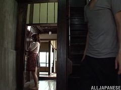 Busty Japanese mom is talking on the phone in the hall. A guy comes up to her from behind, puts his hand into her pantyhose and pleases the woman with fingering.
