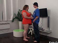 This chick is obese and has huge boobs. She sucks on a skinny dude's dick before she sits on it. She rides his stiff dick reverse cowgirl as good as she can.