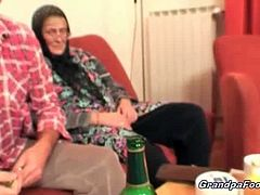 Nasty dark haired babe gives hot massage to this old stud. She makes him horny and helps his wife in satisfying his cock on the couch. The granny knows how to suck.