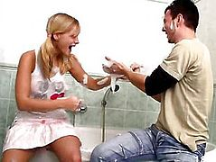 The girl plays with a guy sitting in a bath