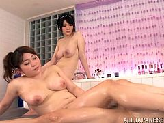 Watch these horny Asian babe giving this guy an oil massage and taking turns sucking and fucking him in this great threesome.