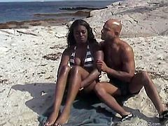 Elegant leggy chick with awesome body wearing hot bikini approaches horny dude who sits on the beach. She seduces him to get her moist poontang drilled doggystyle.