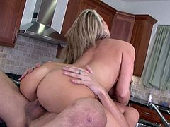 Carolyn Reese is one hot housewife with appetizing curves! Horny dude bends her over the kitchen counter and fucks her hard from behind. Then she rides his hard cock in cowgirl position.