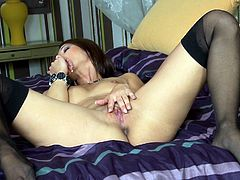 A delightful brunette girl in a sexy lingerie and stockings makes hot solo show in a bedroom. She licks her fingers and fondles the pussy lying on a bed.