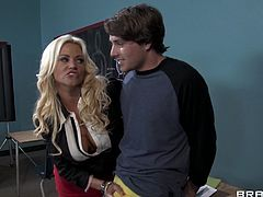 A gorgeous pornstar with long blonde hair, massive natural tits and a shaved pussy enjoys a hardcore threesome fuck in a classroom.