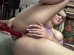 A sexy young blonde with long hair, big tits and a shaved pussy enjoys playing with a plastic cock on her living room floor.